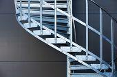 image of spiral staircase  - Fragmetn of modern metal spiral staircase above dark gray wall - JPG