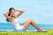 picture of crunch  - Fitness woman exercising doing sit ups outside during exercise training - JPG