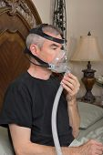 picture of cpap machine  - Man wearing his CPAP machine before sleeping - JPG