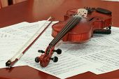 stock photo of mozart  - Violin and notes on the wooden table - JPG