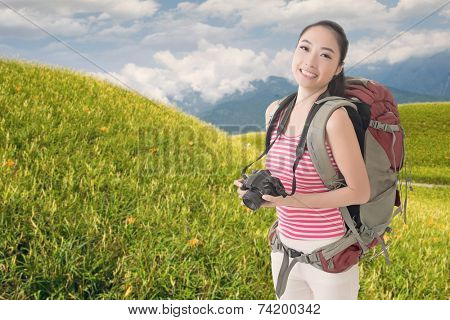 Happy smiling Asian young female backpacker with camera in front of tiger lily farm in Liushidan mountain, Fuli Township, Hualien County, Taiwan, Asia.