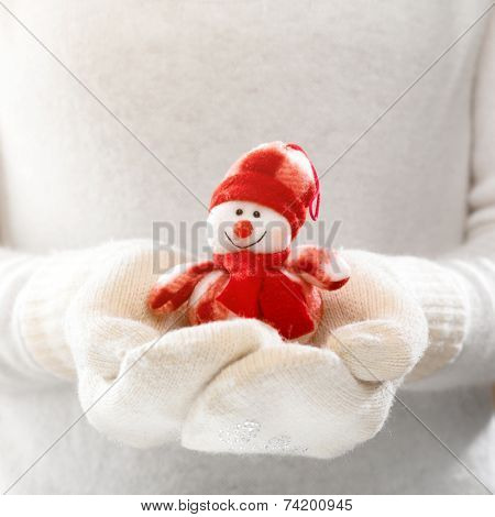 Little toy snowman in female hands in cozy mittens. Woman hands in white mittens holding a cute tiny snowman-toy. Winter time and Christmas present concept.