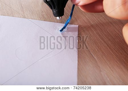 Woman's hand making postcard with blue ribbon with a help of glue gun