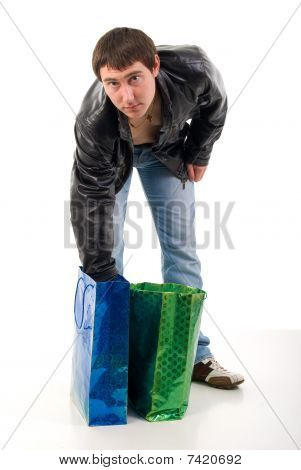Young Guy In Black Leather Jacket And Shopping Bags. Studio Shoot Over White Background.