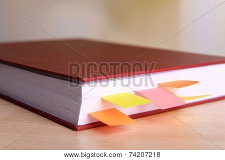 Book with bookmarks on table on bright background