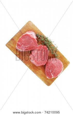 red fresh fillet chops : three raw beef fillet chops on wooden board with thyme twig ready to prepare . isolated over white background