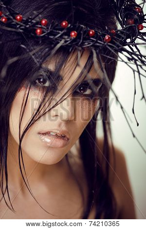 pretty brunette woman with make up like demon at halloween