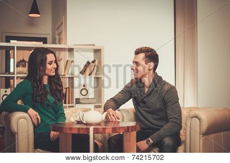Young couple drinking tea during discussion