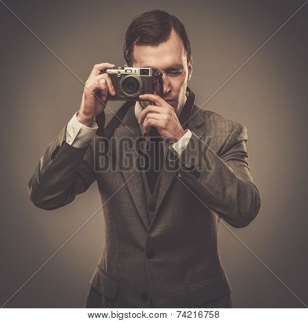 Well-dressed man with a retro camera