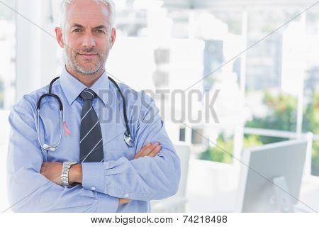 Doctor with arms crossed wearing breast cancer awareness ribbon