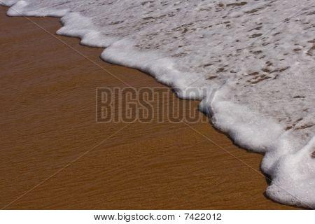 simple foamy wave on sandy beach