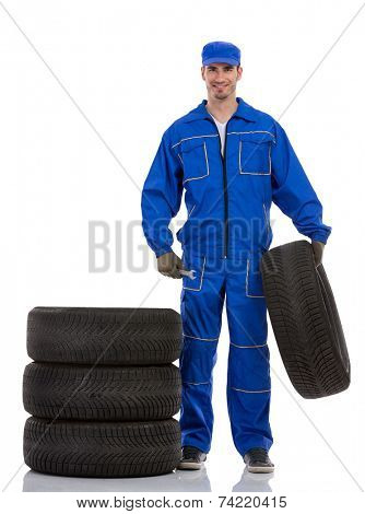 young car mechanic holding car tires on white background