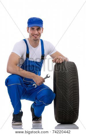 Friendly car mechanic with  tires and wrench