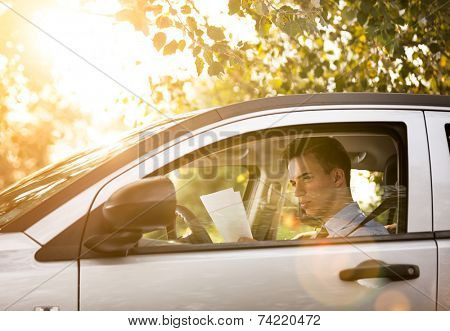 Successful businessman in the car with paper work