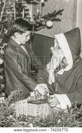 CRANS, SWITZERLAND, DECEMBER 27, 1956: Vintage photo of Santa Klaus giving gift to little boy