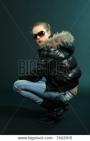 Tough girl in black jacket crouching on dark cyan background