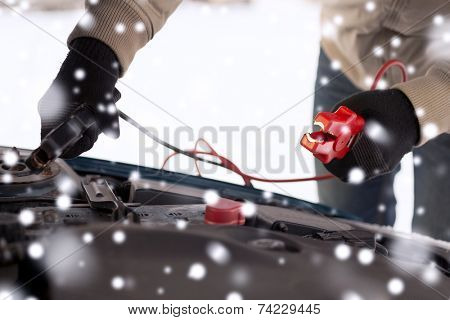 transportation, winter, people and vehicle concept - closeup of man under bonnet with starter cables
