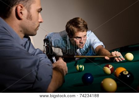 Focused young casual caucasian man playing billiard with friend. Holding cue ready to strike the ball. Concentration, game.