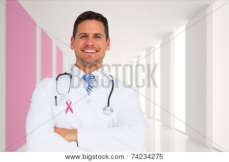Handsome doctor with arms crossed against modern white and pink room with window