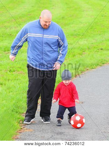 Father and his son playing together with soccer ball.