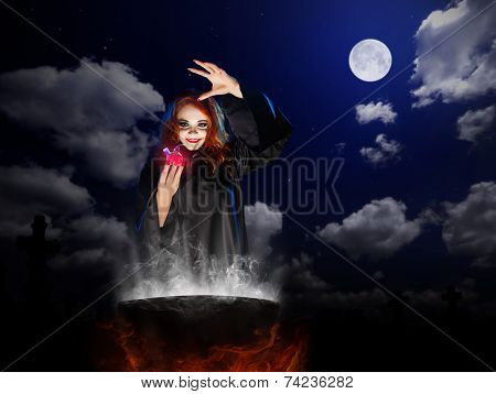 Young witch with red potion and cauldron  at night sky background
