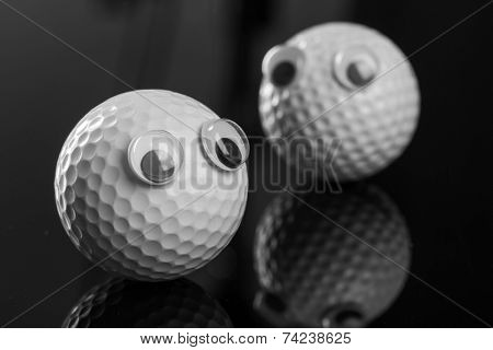 Two golf balls with plastic eyes