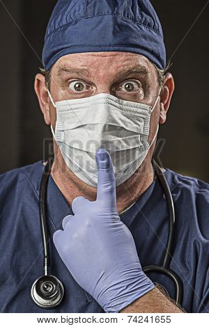 Stunned Doctor or Nurse With Finger in Front of Mouth wearing Protective Wear and Stethoscope.