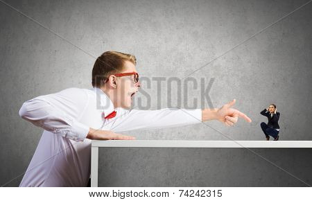 Angry businessman screaming at miniature of woman colleague
