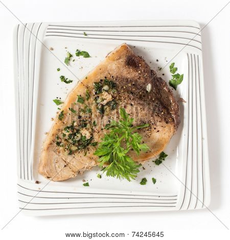 Cooked peppered swordfish steak with a parsley and garlic butter sauce on a plate viewed from above