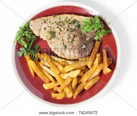 Swordfish steak cooked on a plate with french fries and a parsley and garlic butter sauce seen from above