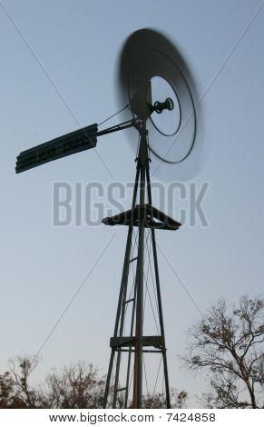 Blurred  Windmill Fan framed by dead trees