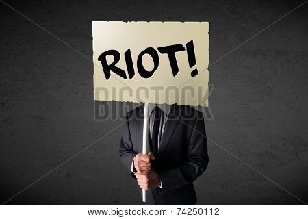Businessman holding a demonstration board with riot sign in front of his head