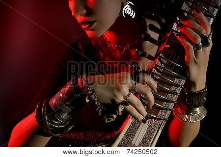 Beautiful Young Indian Woman In Traditional Clothing With Oriental Jewelry Playing The Sitar