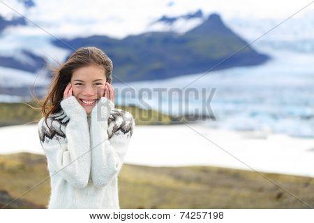 Asian woman portrait by glacier on Iceland wearing Icelandic sweater. Hiker tourist girl smiling cute in nature by glacial lagoon / lake of Fjallsarlon, Vatna glacier, Vatnajokull National Park.