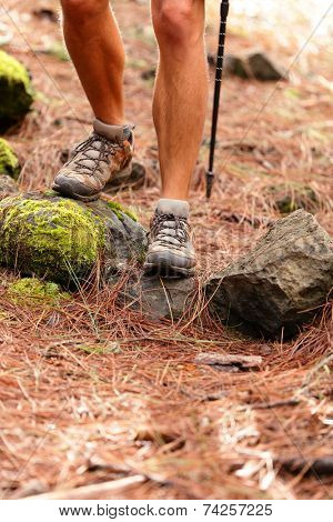 Hiker - close up of male hiking shoes and boots. Man on hike in forest.