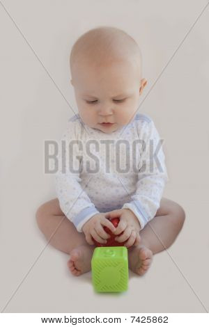 The Kid Plays With Two  Cubes