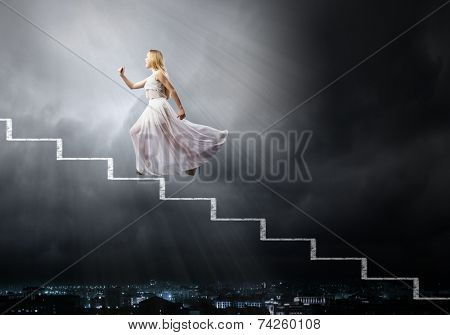 Young woman in white long dress stepping up the staircase