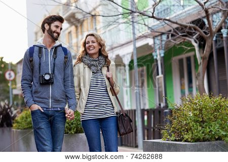 young couple on holiday walking with camera in city having fun vacation in autumn