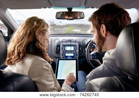 couple using gps on tablet compter to navigate in car on holiday