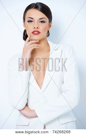 Sensual Young Woman in Sexy White Outfit  Showing Cleavage. Captured in Studio  Looking at Camera with One Hand on the Face. Isolated on White Background.