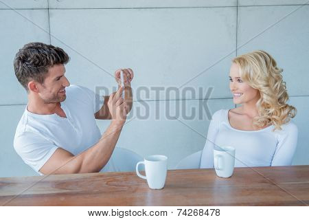 Man taking a photo of his beautiful blond wife on his mobile phone while they sit together at a table enjoying a cup of coffee