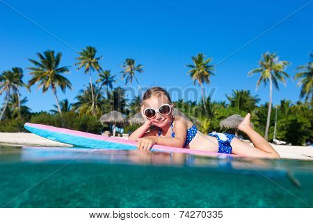 Split underwater photo of adorable little girl on tropical vacation swimming in ocean