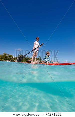 Mother and son paddling on stand up paddle board in tropical ocean