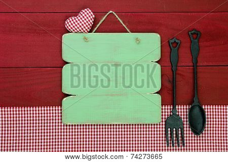 Blank antique green sign by cast iron spoon and fork and red plaid tablecloth