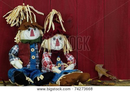 Boy and girl scarecrows sitting by antique red wooden barn