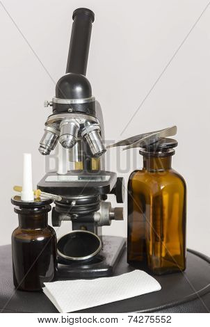 Old Microscope And Two Dark Bottles