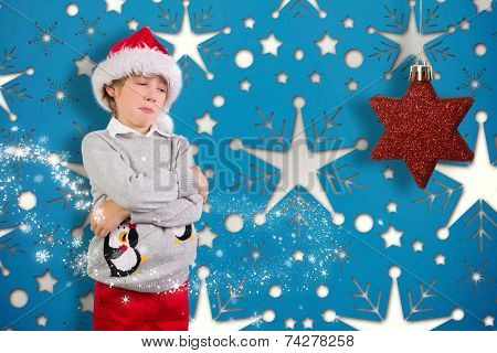 Festive boy sulking against snowflake wallpaper pattern
