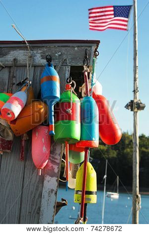 Colorful buoys on a wall of a shack and american flag in Maine, USA