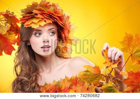 Close-up portrait of beautiful young  girl in in a chaplet from varicoloured autumn leaves on a yellow background