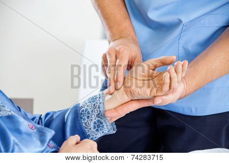 Cropped image male caretaker checking pulse of senior woman at nursing home